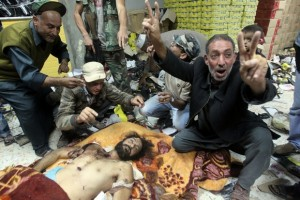 Libyans celebrate over the body of Mutas